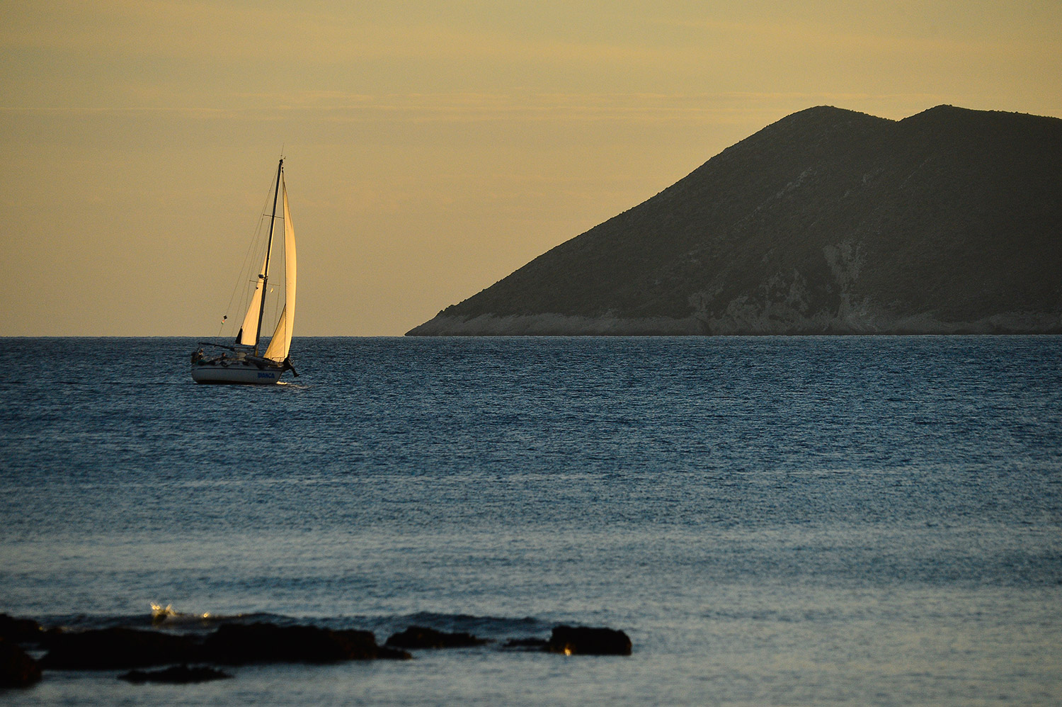 A lone sailboat sails in the sunset between the island of Vis and the island of Biševo