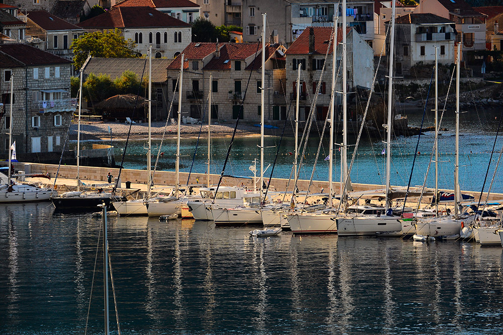 Sailing boats tied to the pier in the bay of Komiža on the island of Vis