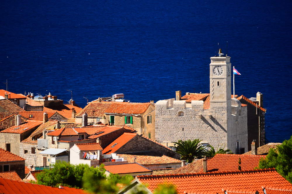 The roofs of the town of Komiža and the castle Grimaldi with the blue sea in the background