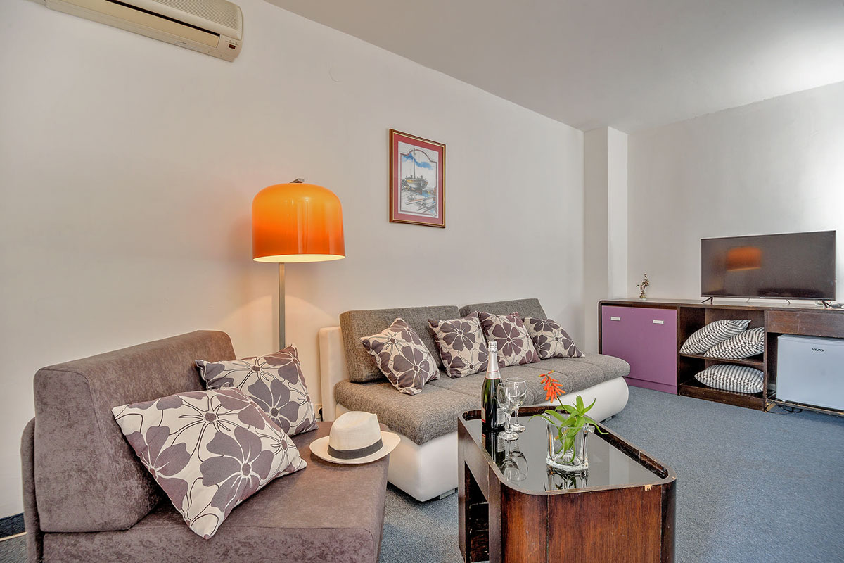 Living area of the hotel apartment with a flat screen TV and a relaxing atmosphere with a bottle of champagne