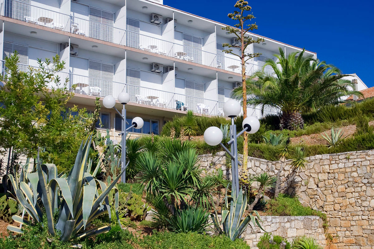 Part of the hotel and its balconies surrounded by a Mediterranean garden