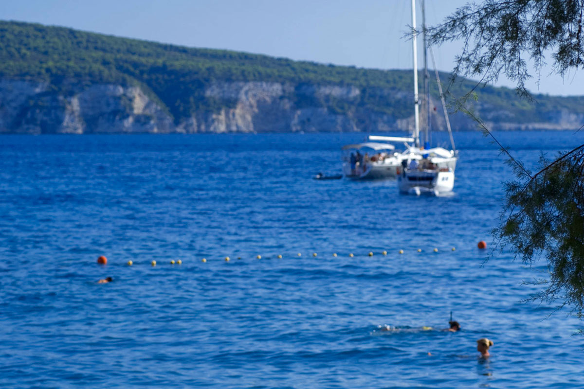 View of the bay of Komiza, the sea and boats, from the beach Gusarica below the Hotel Bisevo