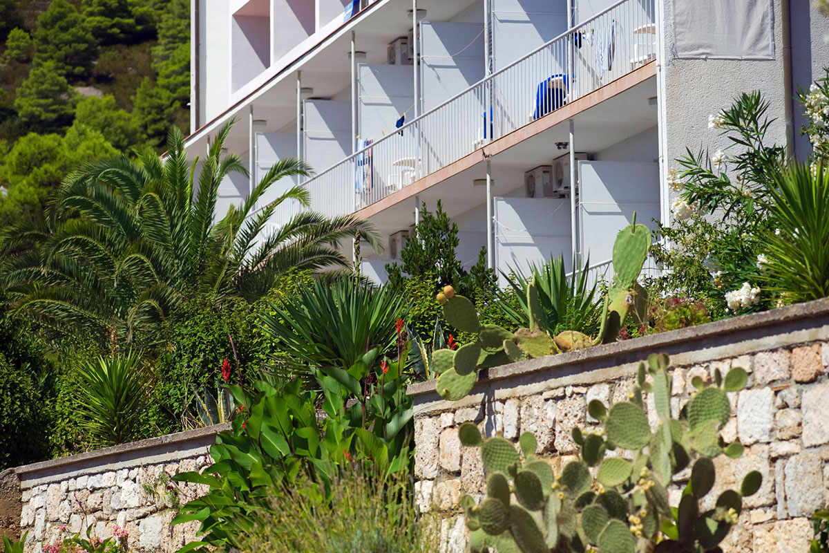 The front of the hotel with balconies and a beautiful Mediterranean garden