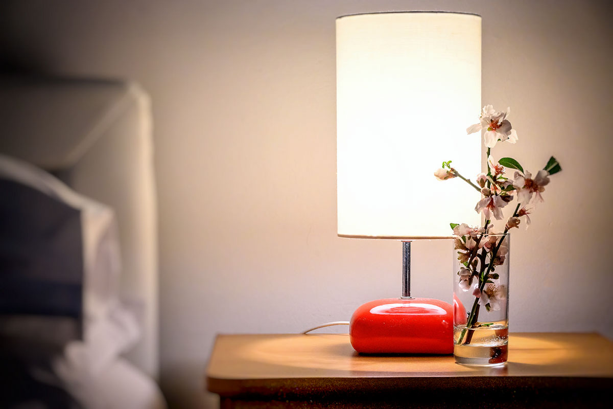 A lamp with a pleasant light and a vase of flowers on the nightstand of the room