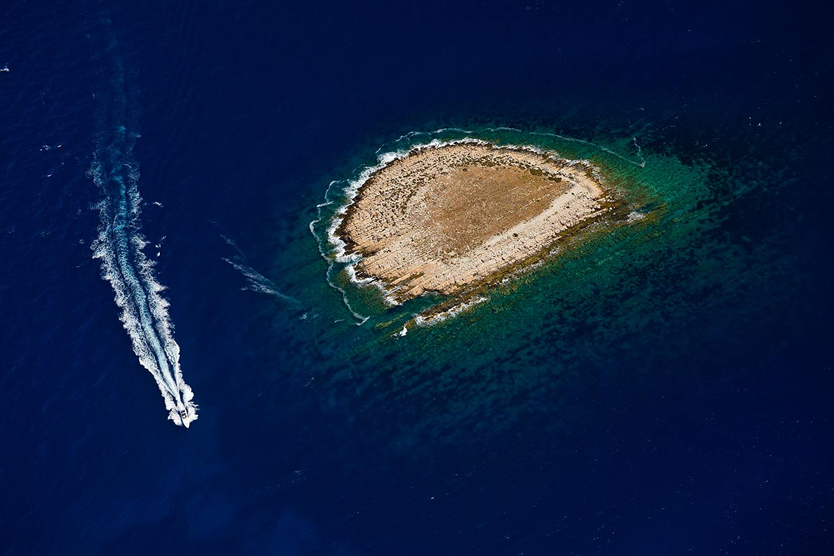 A small island bordered by the sea is part of the Vis archipelago